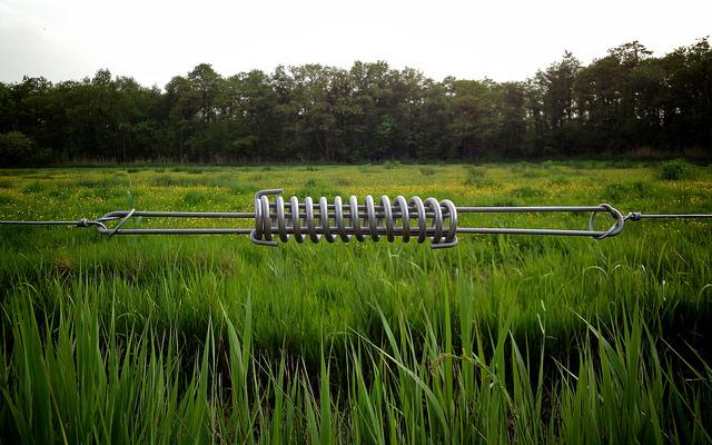 Veer in het ijzerdraad om de afrastering op spanning te houden. Spring loaded iron wire fence.
